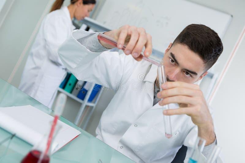 Bioquímico que vierte otro líquido al tubo fotografía de archivo libre de regalías