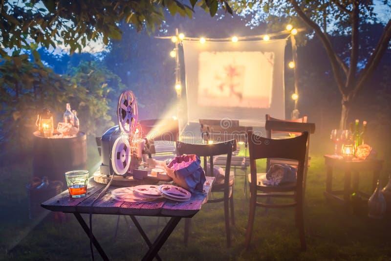 Bioskoop met oude analoge films in de zomertuin de avond stock foto's