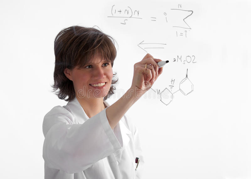 Biotech development with a smile. Attractive, female lab professional working on a chemistry diagram on on a see-through board on white background royalty free stock photo
