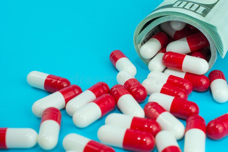 Biotech and pharmaceutical companies. Red white capsules spill out of folded dollars, blue background royalty free stock photos