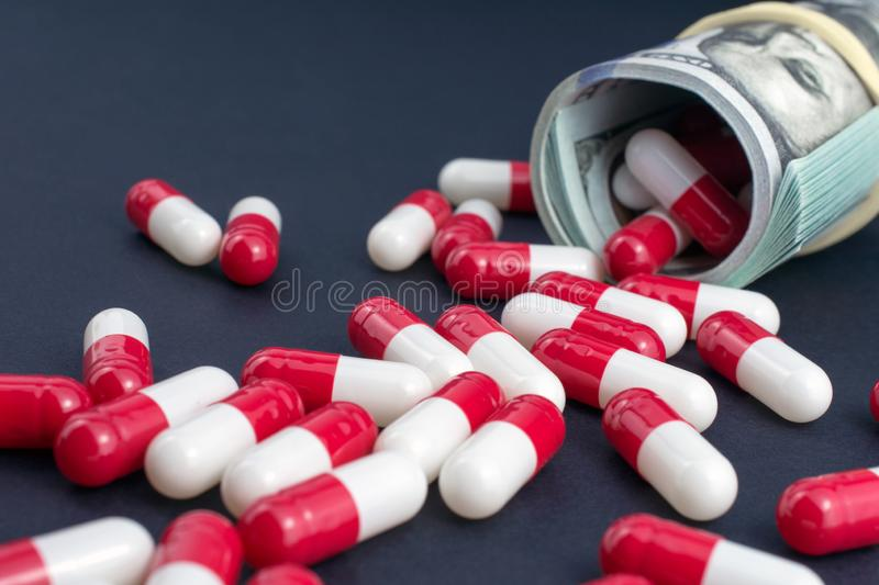Biotech and pharmaceutical companies. Red white pills spill out of folded dollars, dark background stock image