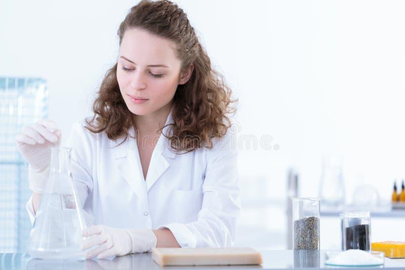 Biotechnologist oplossende steekproef in oplossing stock afbeeldingen