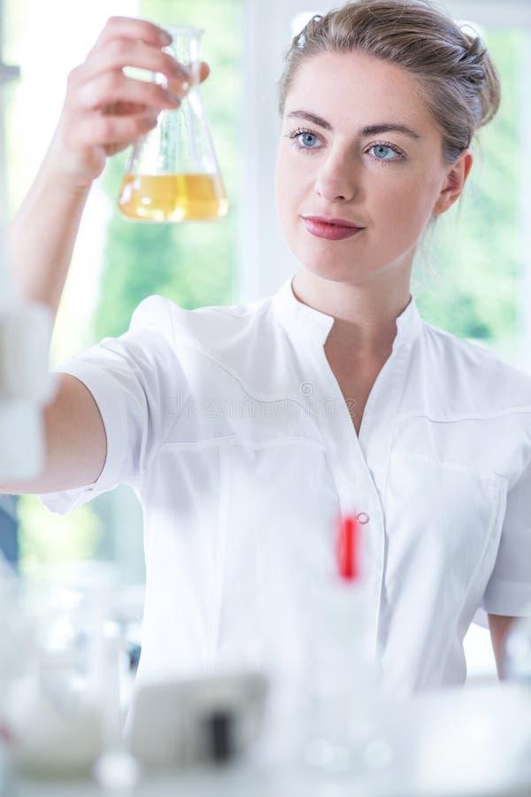 Biotecnologo che analizza sostanza liquida fotografia stock