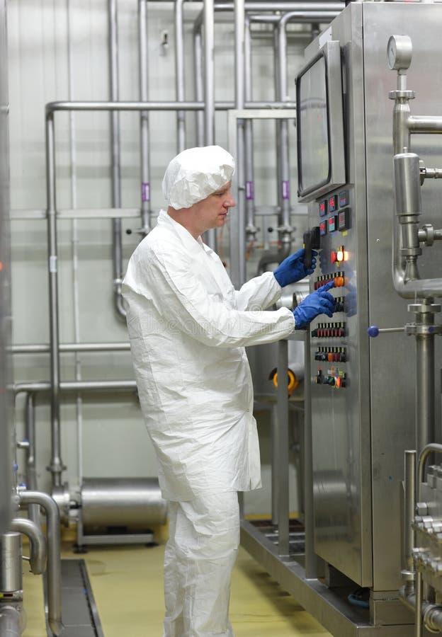 Biotekniktekniker som kontrollerar industriell process arkivbilder