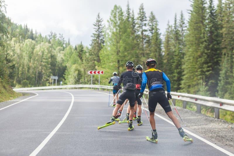 Biotlonists команды идут на лыжи ролика стоковое изображение rf
