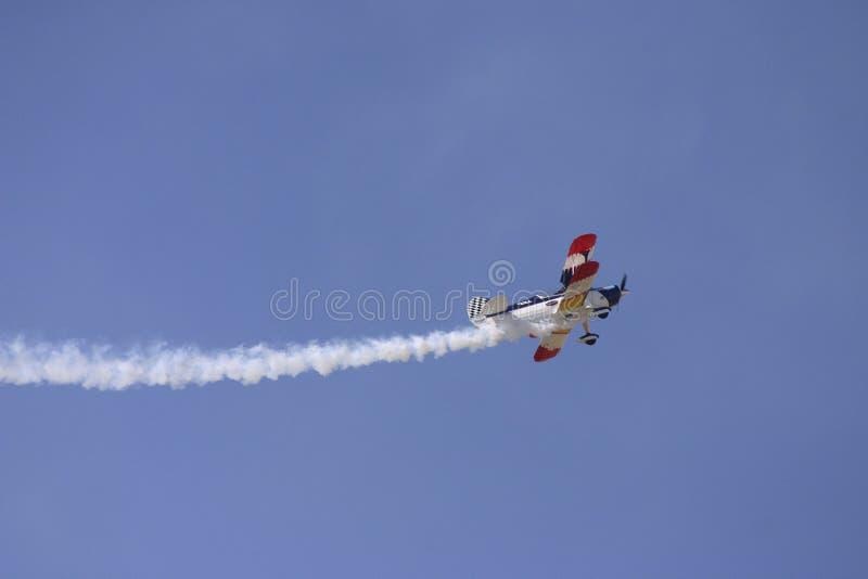 Biplan avec de la fumée de remorquage photographie stock libre de droits