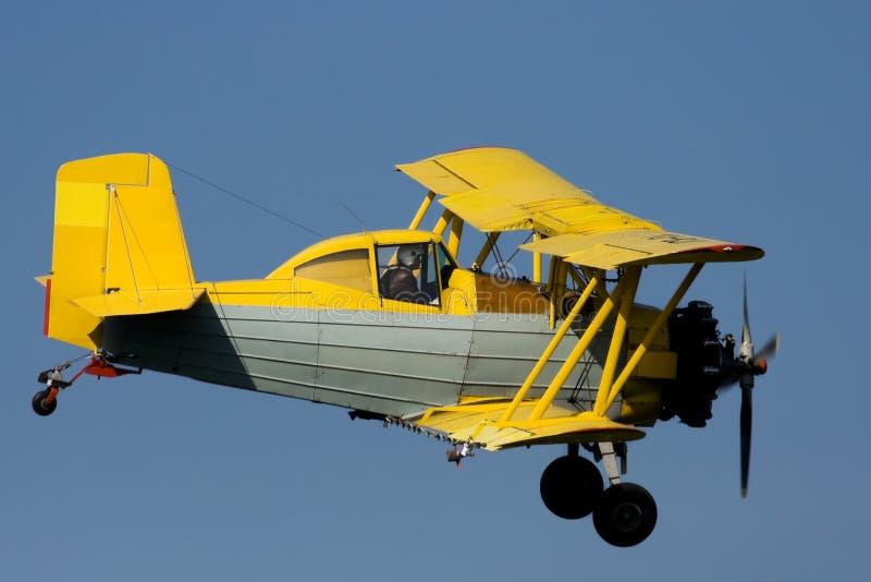 Biplane. Yellow biplane flying on sky royalty free stock image