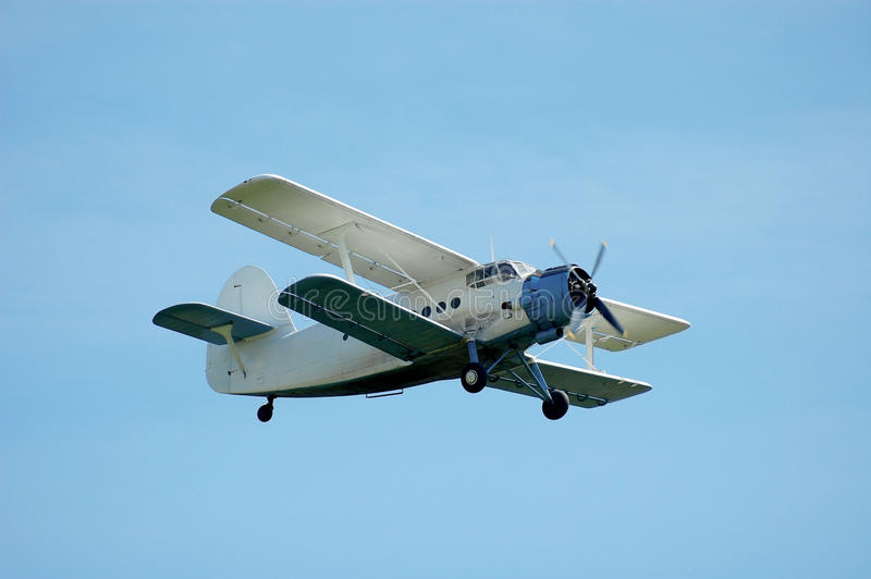 Biplane aircraft. On blue sky background stock images