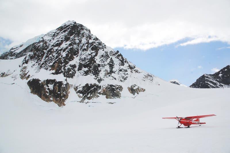 Biplane in alpine field royalty free stock photo