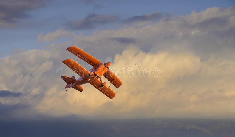 Biplane. Flying through the clouds at dusk royalty free stock image