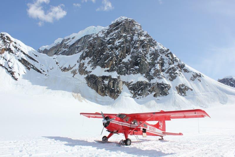 Biplane on snowy mountain royalty free stock photo