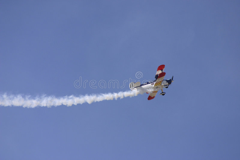 Biplane with trailing smoke royalty free stock photography
