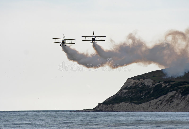 Biplane wingwalkers. Utterly butterly wing walkers display team 2 1940 s super stearman biplanes with daredevils on the top wing of the aircraft royalty free stock image
