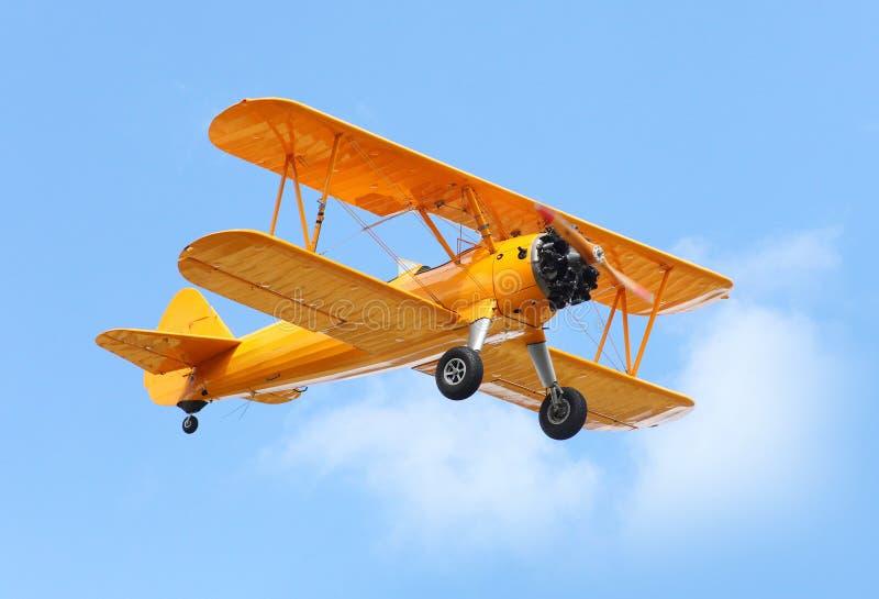The Biplane. Yellow biplane on the blue sky. Retro technology theme stock images