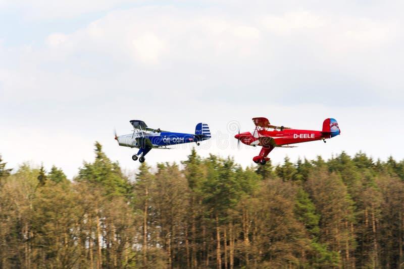 Biplaner som Bucker Bu-131 Jungmann producerade licenserar under, som Tatra T-131 PA som flyger över skog royaltyfri foto
