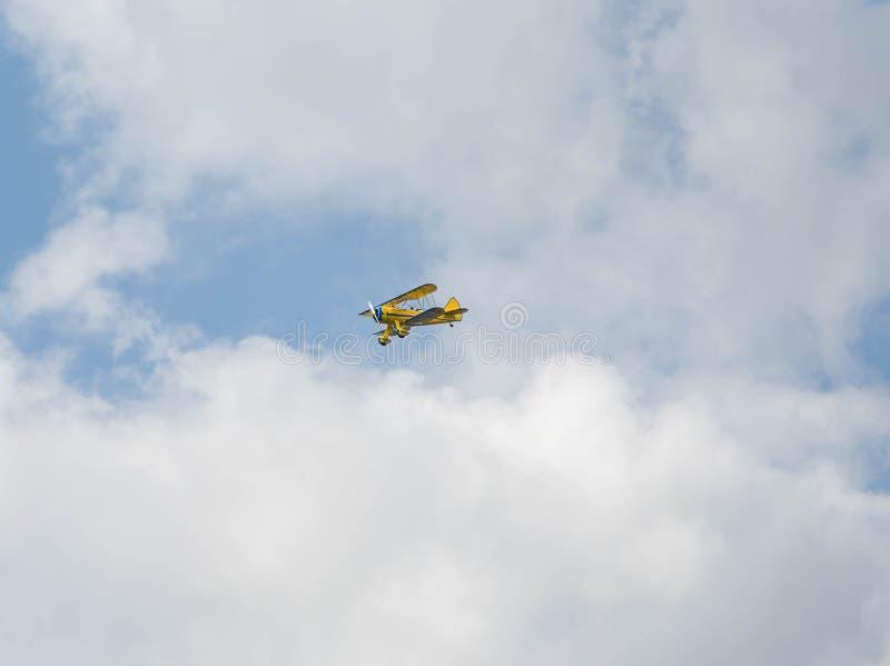 Biplano amarelo em voo imagem de stock royalty free