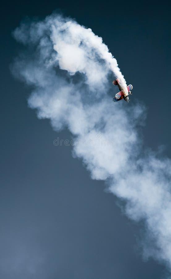 Biplano que muestra la figura de las acrobacias aéreas foto de archivo libre de regalías