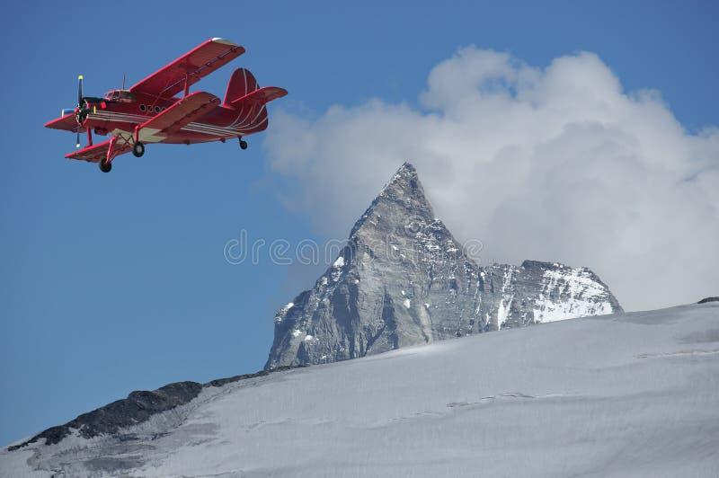 Biplano rosso sopra il Matterhorn fotografie stock libere da diritti