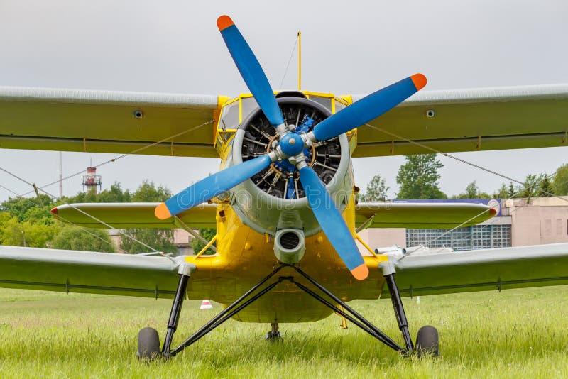 Biplano sovietico Antonov AN-2 degli aerei con l'elica a quattro palette blu e la fusoliera gialla parcheggiate su un'erba verde  immagine stock libera da diritti