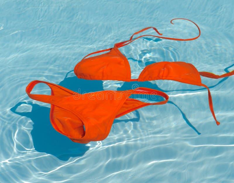Biquini alaranjado na agua potável foto de stock royalty free