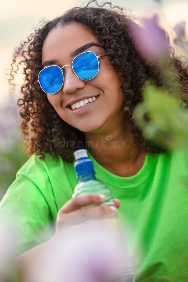 Biracial подросток девушки молодой женщины в поле цветков нося солнечные очки стоковые фото