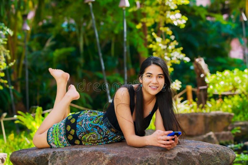 Biracial предназначенная для подростков девушка лежа на утесе смотря мобильный телефон outdoors стоковое изображение