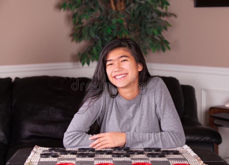 Biracial предназначенная для подростков девушка сидя на доске контролеров стоковое фото rf