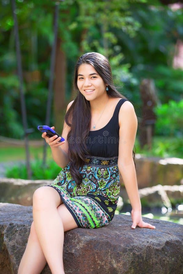 Biracial предназначенная для подростков девушка сидя на утесе смотря мобильный телефон стоковые изображения rf
