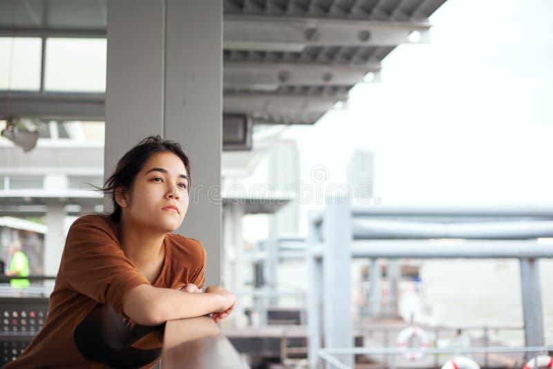 Biracial предназначенная для подростков девушка сидя доком, смотря вверх думающ стоковое фото rf