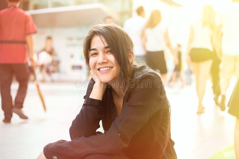 Biracial предназначенная для подростков девушка сидя тротуаром, люди идя в backgr стоковые фото