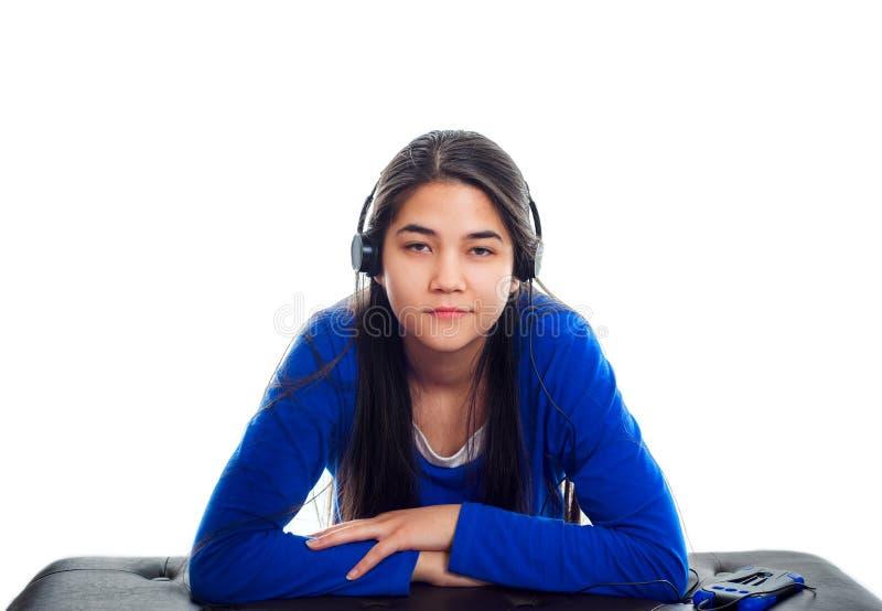 Biracial предназначенная для подростков девушка слушая к музыке на наушниках стоковые изображения