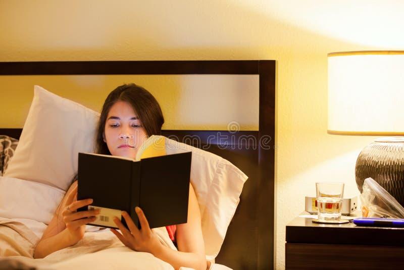 Biracial предназначенная для подростков книга чтения девушки в кровати на ноче стоковые фото