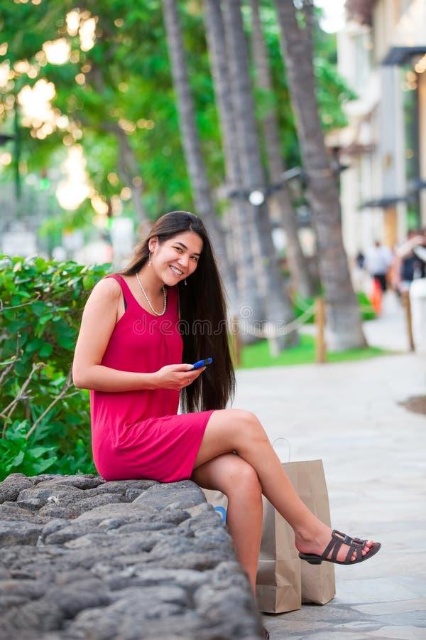 Biracial предназначенное для подростков в красном платье при мобильный телефон сидя в Гаваи стоковое фото rf