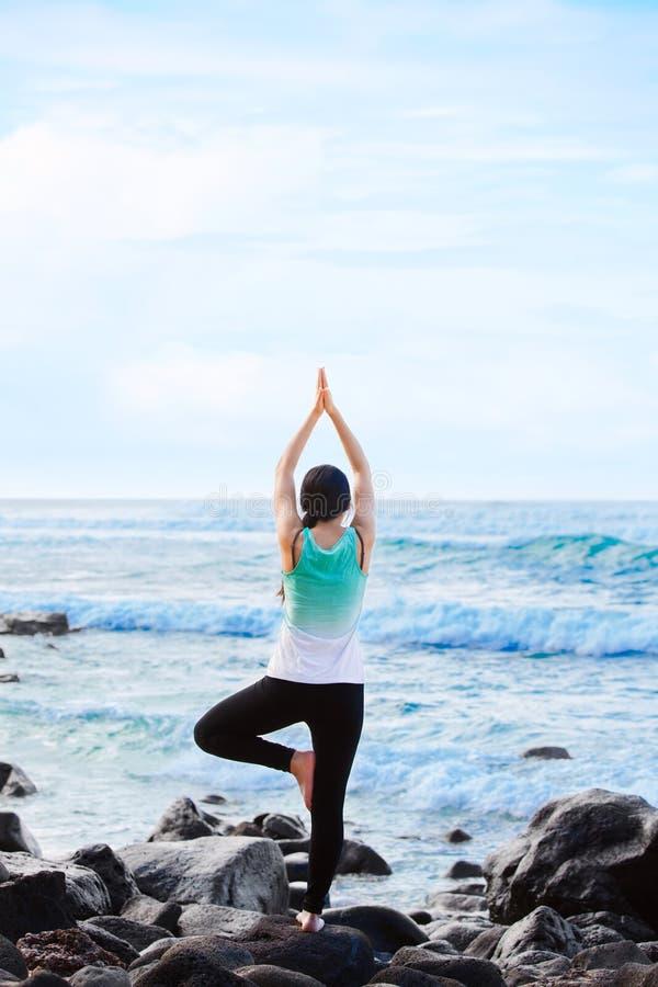 Biracial предназначенное для подростков положение на утесе океаном делая йогу стоковые изображения rf