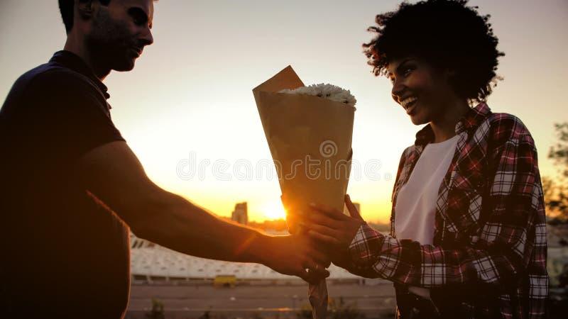 Человек представляя букет белых цветков к biracial девушке на на открытом воздухе дате стоковые изображения
