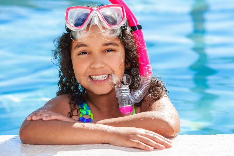 African American Biracial Girl Child In Swimming Pool. Biracial African American happy young girl child relaxing on the side of a swimming pool wearing pink royalty free stock photos