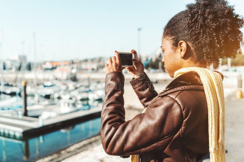 Biracial flicka som fotograferar hamnplatsen royaltyfria bilder