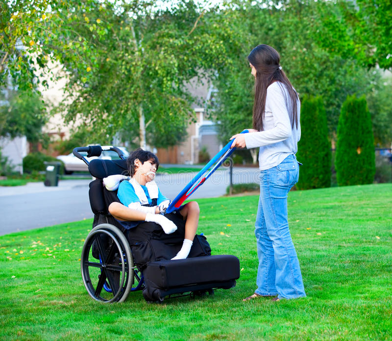 Biracial het oudere zuster spelen in openlucht met gehandicapt weinig brot stock afbeelding