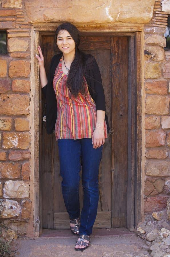 Biracial jugendlich Mädchen, das im Ziegelsteineingang des Hauses steht stockfotografie