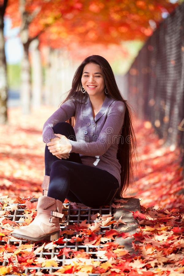 Biracial jugendlich Mädchen, das unter bunten Ahornbäumen im Herbst sitzt stockbild