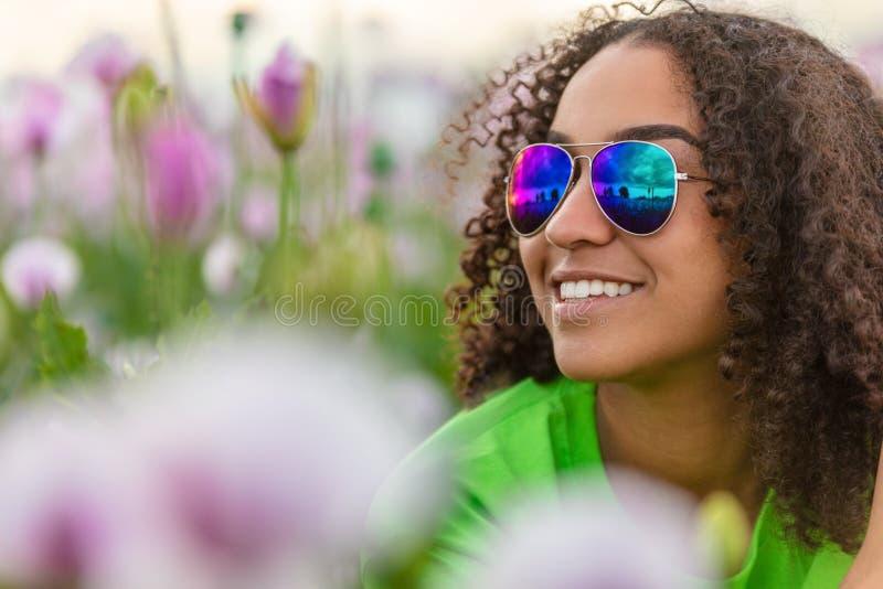 Biracial młodej kobiety dziewczyny nastolatek Jest ubranym okulary przeciwsłonecznych w polu kwiaty zdjęcie royalty free