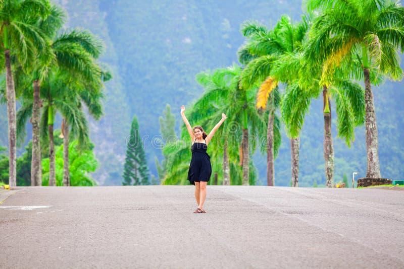 Biracial nastoletnia dziewczyny pozycja w środku drzewko palmowe wykładał ulicę obrazy stock
