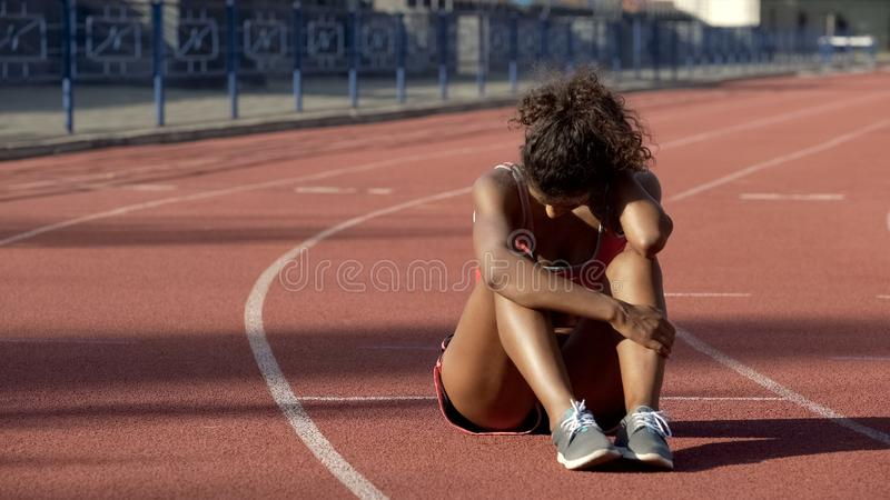 Biracial sportswoman exhausted after tough trainings sitting in middle of track. Stock photo royalty free stock photography