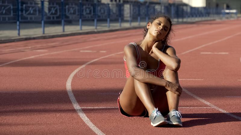Biracial sportswoman sitting tired after trainings in middle of track, exhausted stock photo