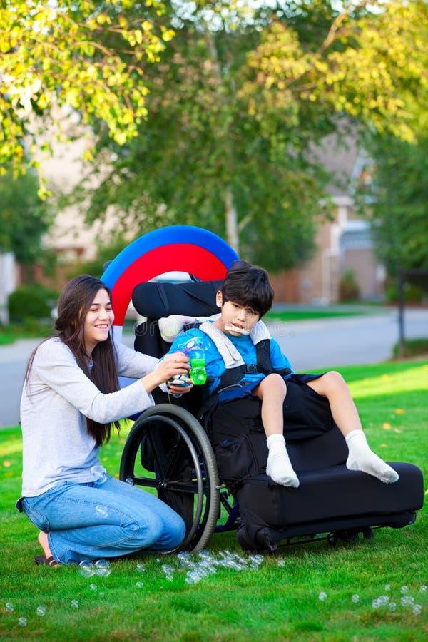 Biracial stara siostra bawić się outdoors z niepełnosprawnym małym brot zdjęcia royalty free