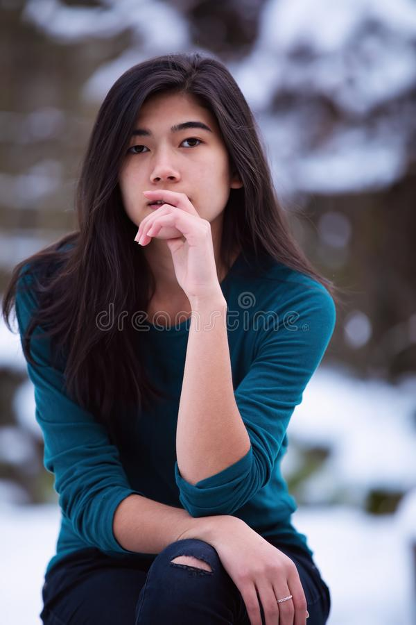 Biracial teen girl sitting on stool outdoors in winter stock image
