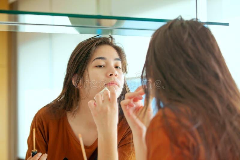 Biracial tonårig flicka som sätter makeup på i spegel royaltyfri fotografi
