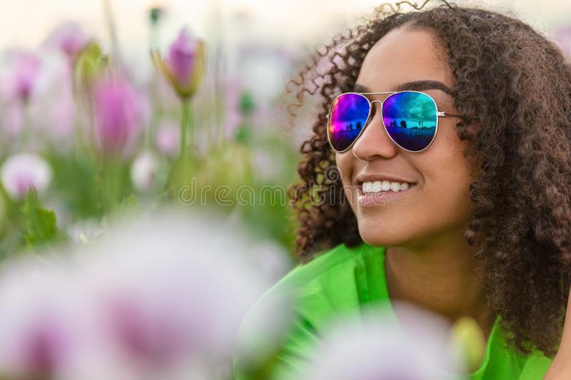 Biracial Young Woman Girl Teenager in Field of Flowers Wearing Sunglasses royalty free stock photo