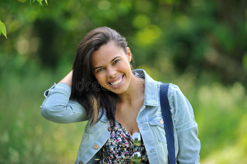 Biracial young woman smiling in the country. Stunning young biracial (African American and Caucasian) woman in the country wearing a sundress carrying a duffel stock photos