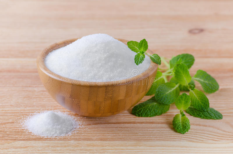 Birch sugar xylitol in a wood bowl with mint on wooden. Background stock photo